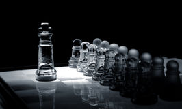 Crystal  chess board and figures. Crystal shess fugures on row against the king,on black background Stock Image