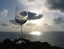 Crystal clear. Empty glass of wine with clouds on the background Stock Image