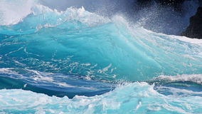 Crystal clear blue wave close-up. Crystal clear blue waves hit the black lava cliffs on the island of Oahu, in Hawaii Royalty Free Stock Image