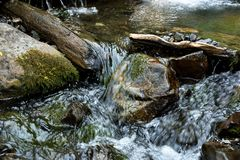 Crystal clear fast moving mountain stream. Flowing from melting snow pack in the in Challis national forest Idaho, smooth boulders and fallen trees surround Royalty Free Stock Images