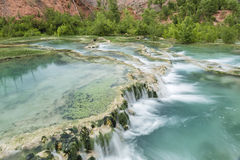 Blue turquoise waterfall on red travertine stock photo - Crystal pools waterfall ...