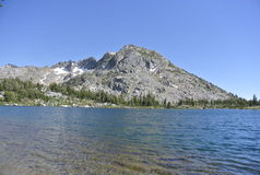 Crystal clear lake under a large granite mountain Royalty Free Stock Image