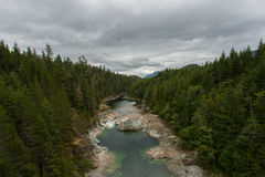 Crystal Clear River on Cloudy Day. Crystal clear river meanders through a thick pine forest under cloudy grey skies Stock Photography