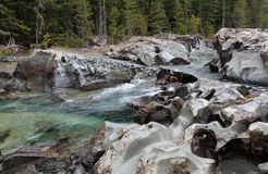Crystal Clear River Traversing Eroded Boulders Stock Photo