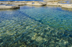 Salt pans. In Gozo forming water reflections and patterns Royalty Free Stock Photo