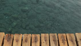 Crystal clear sea water, view from a wooden pier.  stock video footage