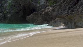 Crystal clear sea waves splashing on sandy shore on cliff background. Turquoise ocean water on cliff island. Blue seaea. Waves on tropical beach stock video footage