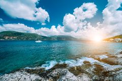 Crystal clear transparent blue turquoise teal Mediterranean sea water in Fiskardo town. White yacht in open sea at Stock Photo