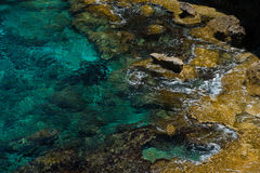 Crystal clear turquoise sea water background and rocky coast Stock Image