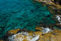 Crystal clear turquoise sea water background and rocky coast Stock Photo