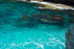 Crystal clear turquoise sea water background and rocky coast Royalty Free Stock Photography