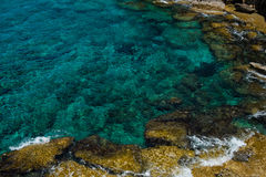 Crystal clear turquoise sea water background and rocky coast Royalty Free Stock Images