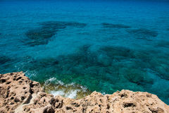 Crystal clear turquoise sea water background and rocky coast Royalty Free Stock Photo