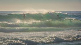 Surfers ride a big wave in windy conditions royalty free stock photography