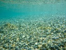 Crystal clear water and a beautiful mosaic of white shiny pebbles scattered off the seabed of the Ithaca island coast, Molos Gulf. Ionian Sea, Greece royalty free stock images