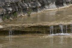 Crystal Clear Water, der über ein kleines, Felsenleistenwasserfall fließt stockbild