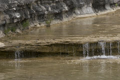Crystal Clear Water flowing over a a small, rock ledge waterfall. Crystal clear waters of Cow Creek in the South Texas Hill Country flowing peacefully over a Stock Image