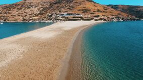 Crystal clear water of mediterranean Aegean sea and sandy coast line. Of Kolona beach of Kythnos island. Slow movement over surface towards the mountain with stock video