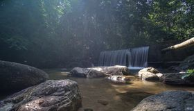Crystal clear water with waterfall in the forest. Crystal clear water near the forest with waterfall over ray of light Royalty Free Stock Photos