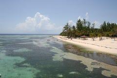 Crystal Clear Water und Tropeninsel-Strand mit Tiki Hut Lizenzfreies Stockfoto