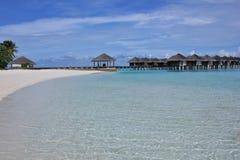 Crystal clear water and water villas, Maldives. White sand beach on Maafushivaru island with its water villas. Ari Atoll, Maldives Stock Image