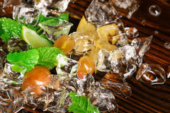 Crystal cold ice cubes. Ice with yellow berries, lime segments, carambola and mint twigs. Ingredients for summer cocktails. Stock Photos
