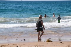 Crystal Cove, California - October 8, 2018: Young girl with her shoes tied to her backpack is seen walking along the beach near th royalty free stock photography