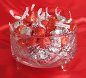 Crystal dish of chocolate kisses. Cut crystal dish filled with chocolate kisses wrapped in red and silver Stock Photo