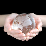 Crystal Earth. In hands isolated on black ground Royalty Free Stock Image