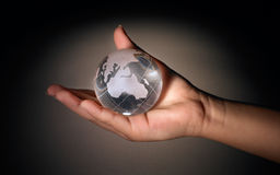 Crystal earth ball. Hand holding crystal earth ball in black background Stock Photography