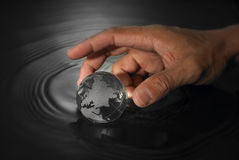 Crystal earth ball. Hand reaching crystal earth ball in black background Stock Image