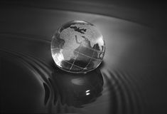 Crystal earth ball. With water reflection in black background Stock Photos