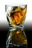 Crystal exponeringsglas med krökta kanter med gamla skotsk whisky och stycken av is Royaltyfri Foto