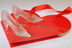 Crystal fancy shoes for cinderella. On a souvenir package in form red heart Stock Images