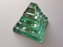 Crystal figure in the shape of a pyramid in semitransparent green water color stock photos