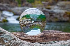 Crystal glass ball sphere reveals nature landscape in macro view royalty free stock image