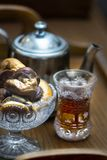 Wooden tray with a teapot and a crystal glass with tea stock photography