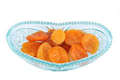 Crystal glass bowl with dried apricots. Crystal glass bowl full of dried apricots isolated on white Royalty Free Stock Images