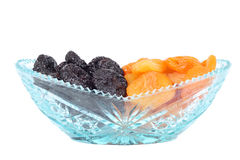 Crystal glass bowl with dried plums and apricots. Crystal glass bowl full of fresh dried plums and apricots isolated on white Stock Photo