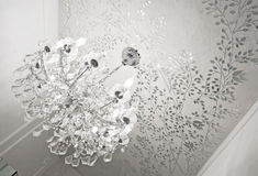 Crystal glass chandelier. Massive crystal glass chandelier on artsy mirror foliage ornament ceiling stock images