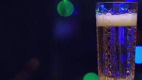 Crystal glass. Filling a crystal glass of champagne on the background of blurred lights stock video footage