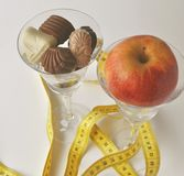 Crystal glass full of chocolates and an apple -new year`s resolutions. Crystal glass full of chocolates and an apple, measuring tape, copy space - new year`s Royalty Free Stock Image