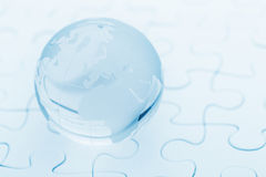 Crystal glass globe ball on puzzle. Crystal glass globe ball on white puzzle Stock Images