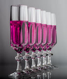 Crystal glass with pink fluid. Six elegant crystal glass with pink liquid online Stock Photography