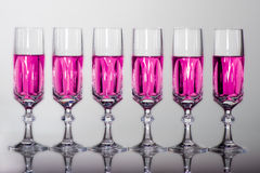 Crystal glass with pink fluid. Six elegant crystal glass with pink liquid online Royalty Free Stock Images