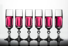 Crystal glass with pink fluid. Six elegant crystal glass with pink liquid online Stock Photos