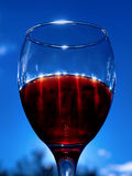 Crystal glass of red wine against blue sky. Crystal glass of red wine with sun reflections against bright blue sky Royalty Free Stock Photos