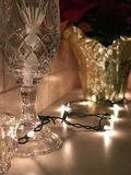 A crystal glass sits in front of holiday and Christmas decorations Stock Image