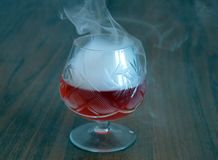 Glass, drink, cocktail, alcohol, red, wine, beverage, martini, isolated, liquid, fruit, dessert, white, cold, food, ice, strawberr. Crystal glass with smoke Royalty Free Stock Photo