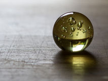Crystal Glass sphere yellow. Crystal glass sphere on the table Royalty Free Stock Image